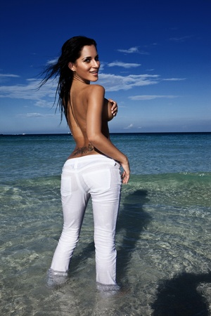 Sexy Voluptuous Topless Woman posing in the ocean in jeans looking back over her shoulder, hand covering nipple Stock Photo - 12600940
