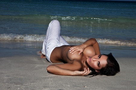 beach breast: Topless sexy woman with large breasts partly concealed by her arm lying on a beach alongside the sea. Stock Photo