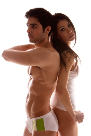 Attractive sexy unsmiling couple dressed in undewear standing back to back, shadowed studio portrait on white
