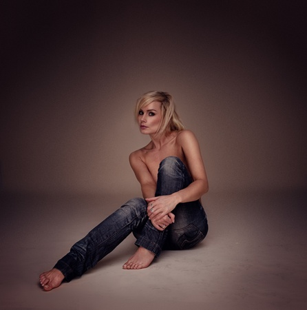 topless jeans: Sexy Casual Blonde Woman seated on the floor implied topless, studio portrait highligted on brown