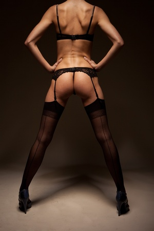 Sexy woman in skimpy black lingerie and stockings standing with her back to the camera and showing her bare buttocks. Stock Photo - 12588495