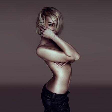 mujer sexy desnuda: De lado sexy rubia mujer sobre a la cámara mirando a través de su cabello con su brazo sobre sus pechos, tetas al aire implicada