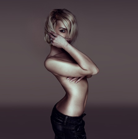 sexy naked woman: Sexy blonde woman sideways on to camera peering through her hair with her arm across her breasts, implied topless Stock Photo
