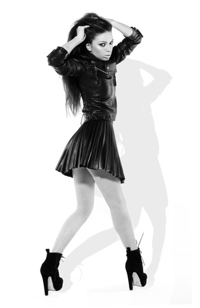Provocative brunette woman in skimpy black leather miniskirt turning back to look at the camera, monochrome image with shadow photo