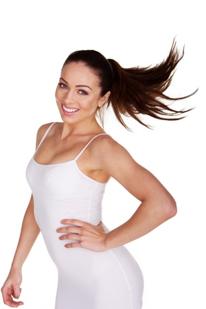 vivacious: Playful vivacious young woman laughing and tossing her long brunette hair isolated on white Stock Photo