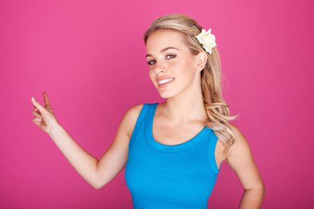 sincere girl: Beautiful smiling blonde woman in blue top pointing with her finger at blank copyspace for your text. Stock Photo