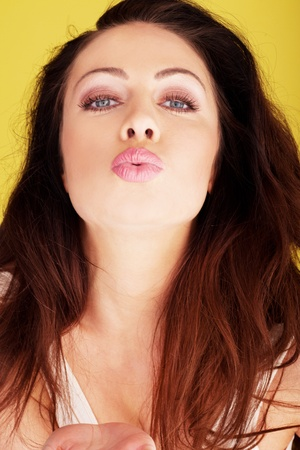 puckered lips: Sexy brunette woman with her lips puckered up blowing a kiss