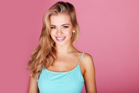 beauty woman: Pretty young woman smiling against a pink background