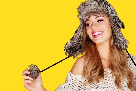 Carefree pretty young blonde woman playing with the pompom on her winter hat.