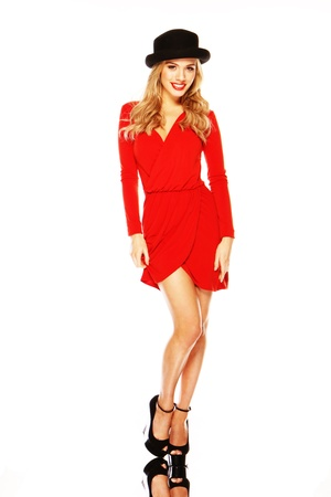 A beautiful blonde fashion model in chic red outfit showing off her long slim legs.