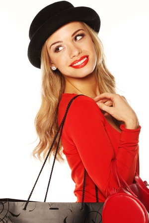 Fashionable blonde woman in chic red outfit and hat giving over-the-shoulder look.