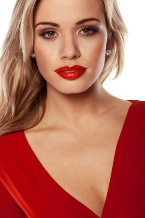 Seductive blonde woman with red lipstick wearing a matching red dress. photo