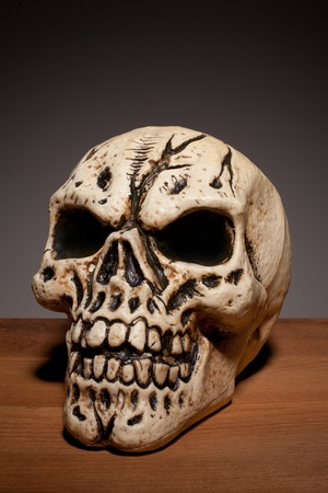 A fake human skull on a wooden board with copyspace, conceptual for Halloween and death. photo