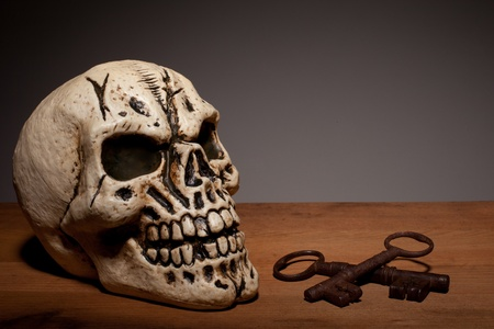 eye socket: Fake human skull with two vintage keys on a wooden board with copyspace.