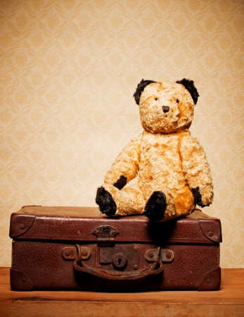 Old vintage teddy bear and old leather suitcase, bygones and memorabilia. photo