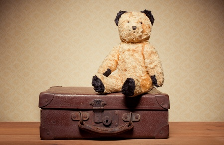 collectors: Childhood Nostalgia Teddy Bear. Old vintage teddy bear and leather suitcase with copyspace.