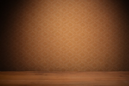 Vintage textured brown wallpaper with heavy vignetting over a wooden floor, empty with copyspace. photo