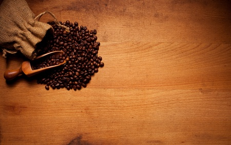 Freshly roasted coffee beans spilling out of a hessian bag over a wooden scoop and onto a textured wooden background with copyspace photo