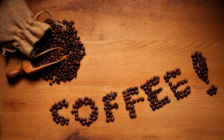 hessian bag: Freshly Roasted Coffee Beans spilling out of a hessian bag onto a wooden surface with the text COFFEE in beans Stock Photo