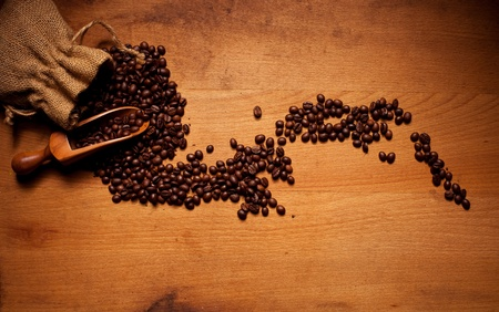 hessian bag: Freshly Roasted Coffee Beans spilling out of a hessian bag over a wooden scoop onto a wooden surface