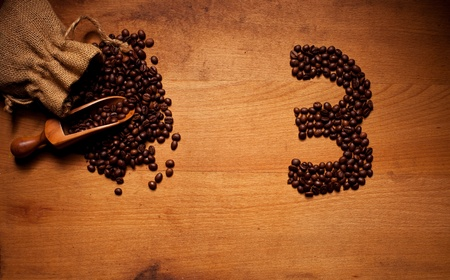 Freshly Roasted Coffee Beans spilling out of a hessian bag onto a wooden surface with a number 3 in beans photo