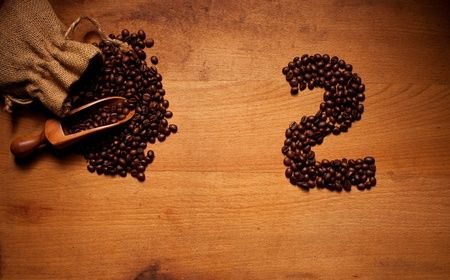 Freshly Roasted Coffee Beans spilling out of a hessian bag onto a wooden surface with a number 2 in beans photo