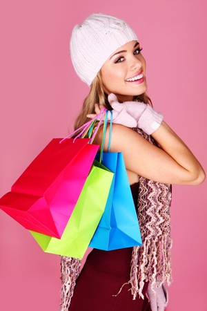 jaunty: Happy Woman Shopper. Beautiful smiling woman carrying colourful carrier bags over her shoulder