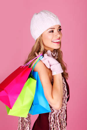 Smiling Woman Out Shopping. Pretty woman with beautiful smile out shopping with three colouful shopping bags photo