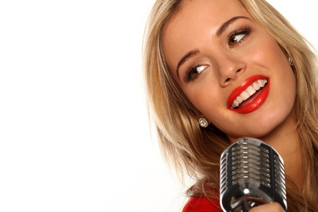 Beautiful young blonde female singer performing with a microphone, isolated studio portrait on white Stock Photo - 12589969