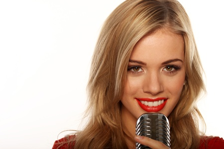 vocalist: Smiling blonde woman holding a microphone to her mouth, closeup studio portrait on white with copyspace.