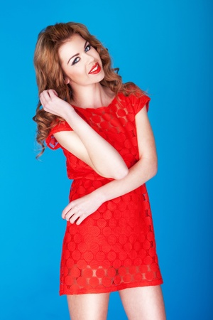 girl in red dress: Attractive Smiling Redhead dressed in a red summer dress posing against a blue studio backdrop.