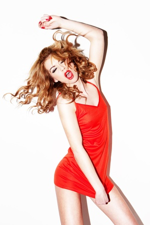 Vivacious redhead singing and dancing in a red miniskirt dress, studio portrait on white.