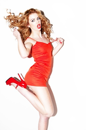Vivacious young redhead woman dancing and kicking her heels in the air with her long wavy hair flying out behind. photo