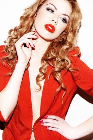 labbra sensuali: Glamourous sofisticata donna rossa che porta attrezzatura rossa e di corrispondenza lipgloss rosso.