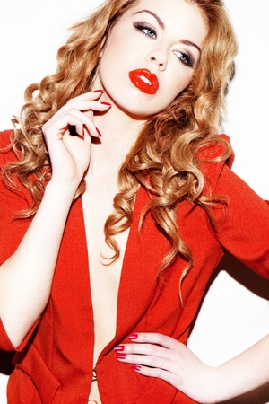 Glamourous sophisticated redhead woman wearing red outfit and matching red lipgloss.