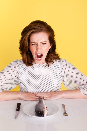 outraged: Fun image of an outraged woman seated at a table showing her disgust at being served a whole raw fish to eat.