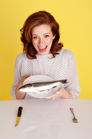 hilarity: Humorous of a laughing redhead woman seated at a table holding a whole raw fish on her plate.