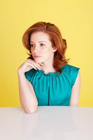 Sad despondent redhead woman seated at a table with her chin on her hand. photo
