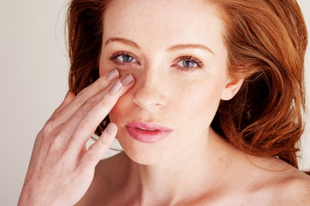 enhance: Attractive redhead woman in beauty portrait blending foundation on to her face with her fingertips