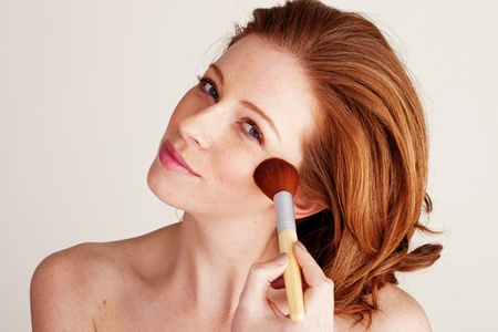 Beautiful redhead woman applying blusher to her cheekbone with a large cosmetics brush Stock Photo - 12588725