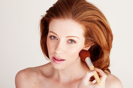 Woman using a large soft cosmetics brush to apply blusher under her cheekbone. Stock Photo - 12588569