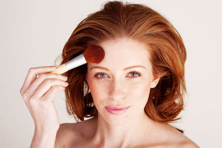 Attractive redhead woman using a large cosmetics brush to apply powder to her forehead. Stock Photo - 12587697