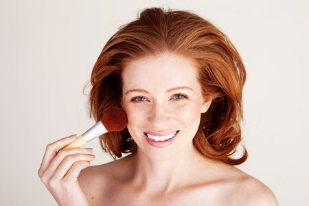 Pretty smiling redhead woman using a large cosmetic brush to apply blusher to her cheekbone. Stock Photo - 12587295