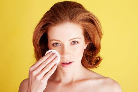 aseo personal: Higiene personal y el concepto de cuidado de la piel con una hermosa mujer limpieza su rostro con un algodón. Foto de archivo