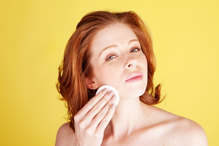 cleanser: A beauty shot of an attractive redhead woman cleaning her face with a cotton pad