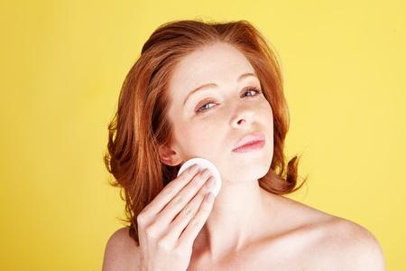 pelirrojas: Un disparo de belleza de una mujer atractiva pelirroja limpiar su rostro con un algod�n