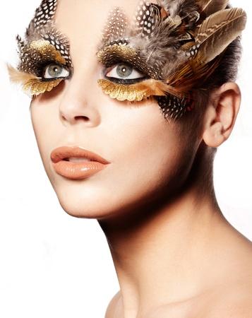 maquillaje de fantasia: Retrato de una bella mujer con maquillaje llamativo ojo creativo con plumas de aves.