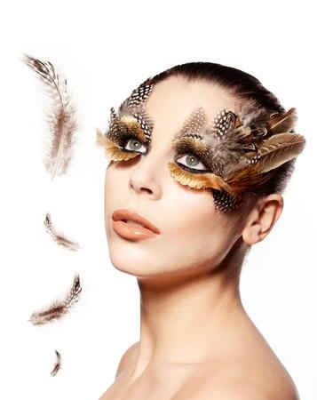 maquillaje de fantasia: Hermosa mujer con maquillaje creativo incorporando plumas de aves con plumas flotando en frente de ella