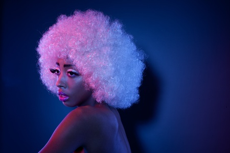 afro hair: Attractive African model in creative makeup and a large curly white Afro style wig looking out of frame with copyspace behind.