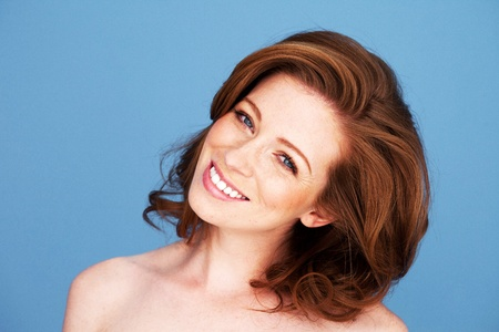 head tilted: Redheadwoman with her head tilted to one side and a beautiful big smile Stock Photo